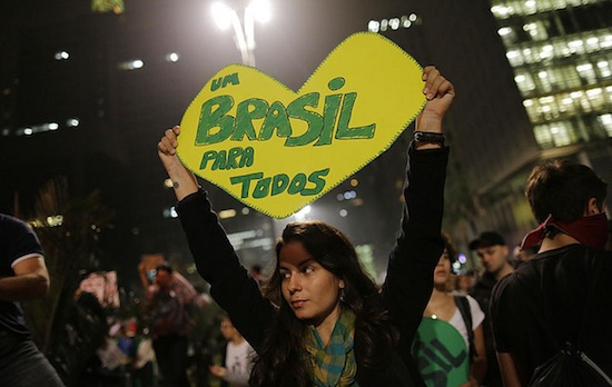 "A woman holds a sign in the shape of a heart saying ""One Brazil for all"" in Portuguese"