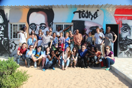 Group of students pose in front of mural of portraits on building in Senegal