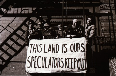 "Eight people standing on building fire escape and holding a sign that says ""This land is ours speculators keep out""."