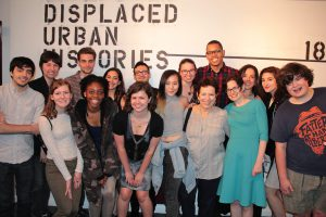 """A class poses in front of the words """"Displaced Urban Histories"""" spray painted onto gallery wall"""
