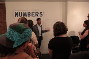 """City Councilman Antonio Reynoso talks to students about """"Numbers"""" portion of exhibit"""