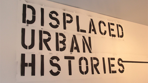 "The words ""Displaced Urban Histories"" spray painted onto gallery wall"