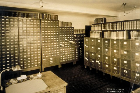 A room with a work desk and filing cabinets with books on top of them lining the walls