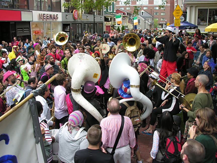 Members of a marching band play for a large crowd on the street