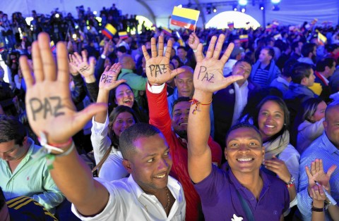 """A crowd of people showing the the word """"Peace"""" written on their palms in Spanish."""