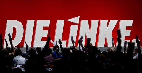 People cheering in front of a sign saying Die Linke