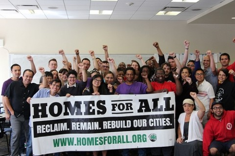 """A group of people raise their left fists in the air while holding a sign saying """"Homes for All Reclaim. Remain. Rebuild Our Cities. www.homesforall.org"""""""