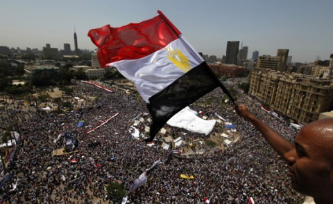 An Egyptian waves a national flag as protesters gather in Tahrir square in Cairo