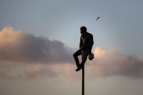Person sitting on top of a streetlight