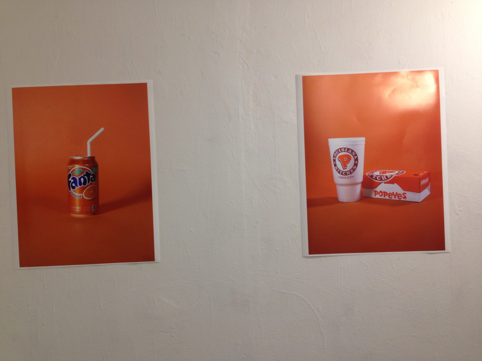 Two photos on wall. Left photo is of an orange Fanta can with a straw. Right picture is a Popeye's chicken meal box and drink.