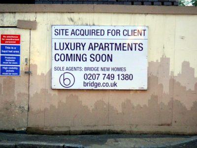 Sign on concrete wall saying site will soon be luxury apartments