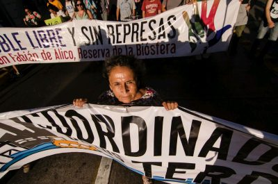 A woman helps to hold up a protest banner