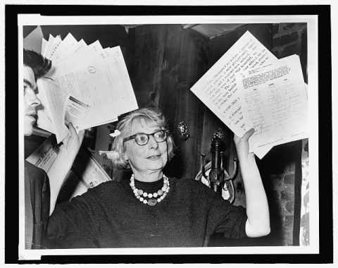 Jane Jacobs holding up documents in both hands