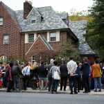 A large crowd of people stand in front of a residential house
