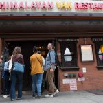 A group of people stand in front of Himalayan Yak Restaurant