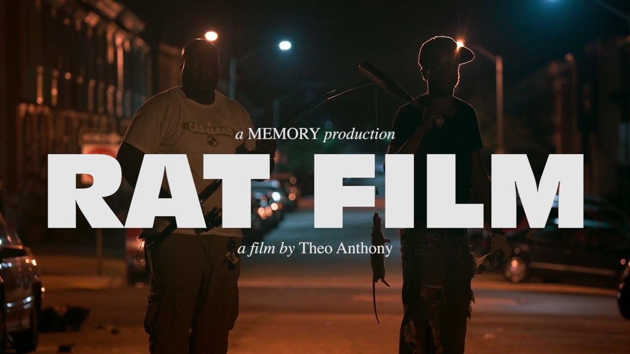 """Two men standing in a city street at night and one is holding a rat for """"Rat Film"""" documentary."""