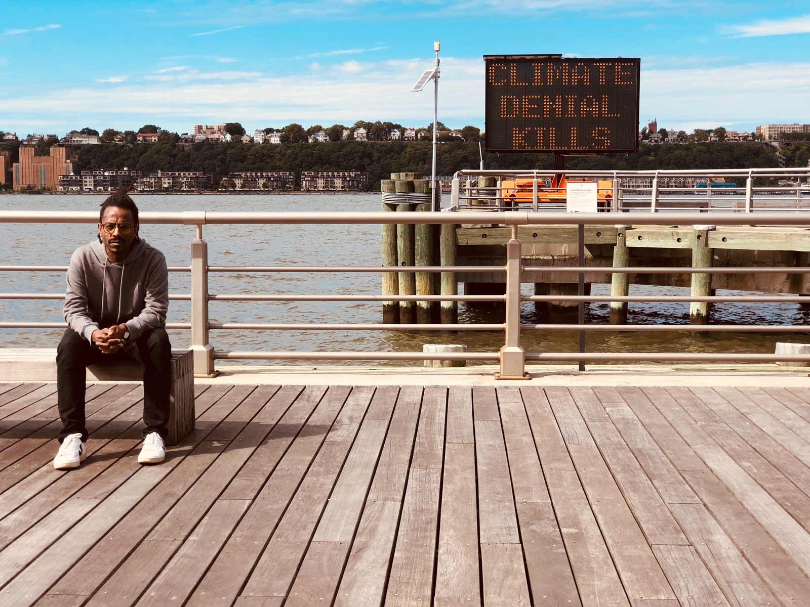 Man sitting on a bench on a boardwalk staring straight into the camera